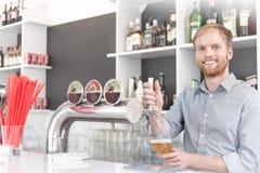Retrato del vidrio de relleno sonriente del camarero joven del golpecito de la cerveza en el restaurante fotos de archivo libres de regalías