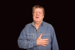 Retrato del viejo hombre con dolor en un corazón en fondo negro Fotografía de archivo