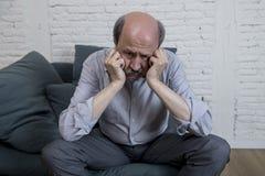 Retrato del viejo hombre maduro mayor en su en casa dolor solo de la sensación del sofá 60s y la depresión sufridores tristes y p Imágenes de archivo libres de regalías
