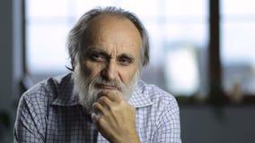 Retrato del viejo hombre pensativo que reflexiona durante vida almacen de metraje de vídeo