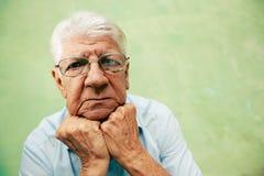 Retrato del viejo hombre serio que mira la cámara con las manos en la barbilla Fotos de archivo