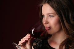 Retrato del vino de consumición de la muchacha Cierre para arriba Fondo rojo oscuro Fotos de archivo libres de regalías