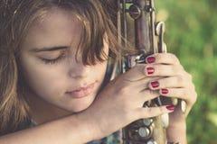 Retrato del vintage de la media cara de una mujer joven con el instrumento musical del viento en la mano en el césped Fotografía de archivo libre de regalías