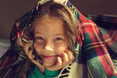 Retrato del vintage de la mirada sonriente adorable linda de la niña hacia fuera de la tela escocesa roja Foto de archivo libre de regalías