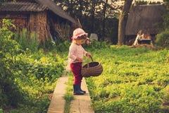 Retrato del vintage del niño lindo feliz con la cesta grande que se divierte en el campo foto de archivo