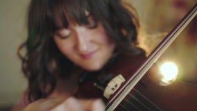 Retrato del violinista atractivo que juega la melodía en viola en dormitorio metrajes