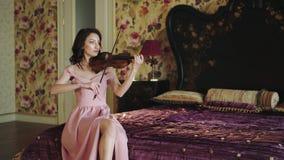 Retrato del violinista elegante que juega la melodía en dormitorio almacen de metraje de vídeo
