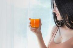 Retrato del zumo de naranja fresco de consumición sano de la mujer asiática joven del vidrio fotos de archivo libres de regalías