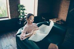 Retrato dela ela perito experiente querido saber chocado atrativo agradável da senhora que senta-se na leitura confortável do sof imagem de stock royalty free
