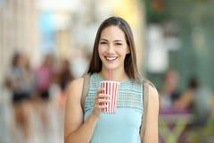 Retrato delantero de una muchacha que lleva a cabo una bebida del llevar Fotos de archivo libres de regalías