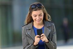 Retrato delantero de una muchacha que usa un teléfono elegante Fotos de archivo