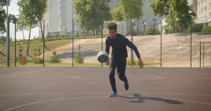 Retrato delantero del primer del jugador de básquet de sexo masculino afroamericano atractivo joven que lanza una bola en un aro  metrajes