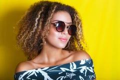 Retrato dentro de una mujer afroamericana joven en gafas de sol Fondo amarillo lifestyle Ropa ocasional Imagen de archivo libre de regalías