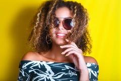 Retrato dentro de una mujer afroamericana joven en gafas de sol Fondo amarillo lifestyle Ropa ocasional Fotografía de archivo libre de regalías