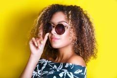Retrato dentro de una mujer afroamericana joven en gafas de sol Fondo amarillo lifestyle Ropa ocasional Imagen de archivo
