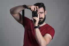 Retrato desaturado del fotógrafo que toma la foto con la cámara del dslr que se sostiene verticalmente Fotos de archivo