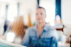 retrato, detalhes para fora borrados de limpeza de janela Detergente e pano do sabão no vidro de janela imagens de stock royalty free