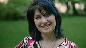 Retrato dianteiro da mulher de sorriso bonita que olha a câmera no parque 4k video estoque