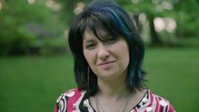 Retrato dianteiro da mulher de sorriso bonita que olha a câmera no parque 4k vídeos de arquivo
