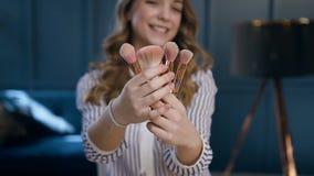 Retrato disparado da mulher considerável que guarda escovas nas mãos e que possing à câmera video estoque