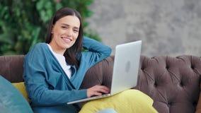 Retrato disparado médio da mulher bonita feliz do freelancer que usa o portátil que olha a câmera filme