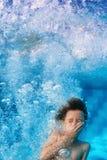 Retrato divertido de la cara del niño sonriente que nada bajo el agua en piscina Foto de archivo