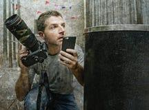 Retrato divertido de la forma de vida del hombre joven del fotógrafo de los paparazzis en la acción ocultado detrás de cesta del  foto de archivo libre de regalías