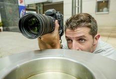 Retrato divertido de la forma de vida del hombre joven del fotógrafo de los paparazzis en la acción ocultado detrás de cesta del  fotos de archivo
