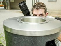 Retrato divertido de la forma de vida del hombre joven del fotógrafo de los paparazzis en la acción ocultado detrás de cesta del  imagenes de archivo