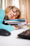 Retrato divertido de la mujer joven desaliñada que duerme en los libros Fotografía de archivo