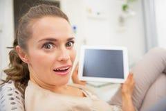 Retrato divertido de la mujer que se sienta en el diván y que usa la PC de la tableta Fotos de archivo