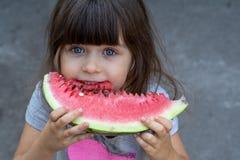 Retrato divertido de los ojos azules de una niña increíblemente hermosa, comiendo la sandía, bocado sano de la fruta imagen de archivo