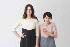 Retrato divertido de pares lesbianos de muchachas jovenes del estudiante en ropa a juego Muchacha de pelo largo que es más alta q Imagenes de archivo