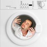 Retrato divertido del hombre dentro de la lavadora Foto de archivo