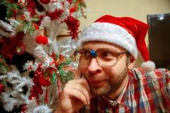 Retrato divertido del inconformista en vidrios y el sombrero de santa cerca del christma Fotografía de archivo