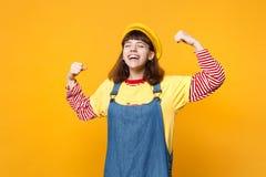 Retrato do adolescente de riso da menina na boina francesa, sundress da sarja de Nimes que mostram os bíceps, músculos isolados n fotografia de stock