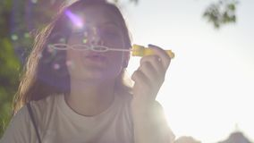 Retrato do adolescente nas bolhas de sabão de sopro do parque na câmera Tempo bonito da despesa da jovem mulher apenas video estoque