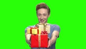 Retrato do adolescente que dá as caixas de presente atuais video estoque
