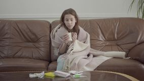 Retrato do adolescente triste envolvido em um assento geral no sofá de couro em casa no fundo dos comprimidos que encontram-se so video estoque