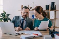 retrato do advogado nos monóculos e no cliente que discutem o contrato no local de trabalho com o portátil imagem de stock royalty free