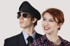 Retrato do aeromoço e do piloto fêmeas felizes contra o fundo cinzento Imagens de Stock Royalty Free