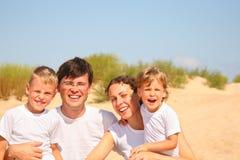 Retrato do agregado familiar com quatro membros na costa arenosa Fotografia de Stock