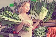 Retrato do aipo, do alho-porro e da alface verdes frescos de compra da mulher Imagens de Stock Royalty Free