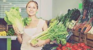 Retrato do aipo, do alho-porro e da alface verdes frescos de compra da mulher Imagem de Stock Royalty Free