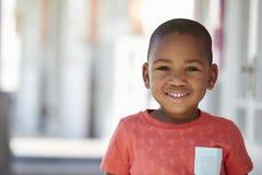 Retrato do aluno masculino fora da sala de aula na escola de Montessori fotografia de stock
