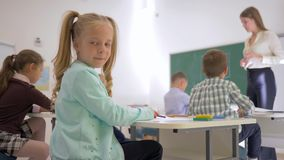 Retrato do aluno na mesa durante a lição de ensino na sala de aula na escola primária em fundo unfocused filme