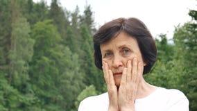 Retrato do ar livre de uma mulher mais idosa com cabelo escuro curto e a cara enrugada que olham a câmera com tristeza no verde video estoque
