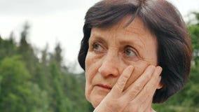Retrato do ar livre de uma mulher mais idosa com cabelo escuro curto e a cara enrugada que pensa sobre a vida só na aposentadoria vídeos de arquivo
