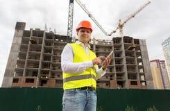 Retrato do arquiteto masculino de sorriso que usa a tabuleta digital no terreno de construção imagens de stock royalty free