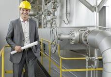 Retrato do arquiteto masculino novo seguro que guarda o modelo pela maquinaria na indústria Imagens de Stock